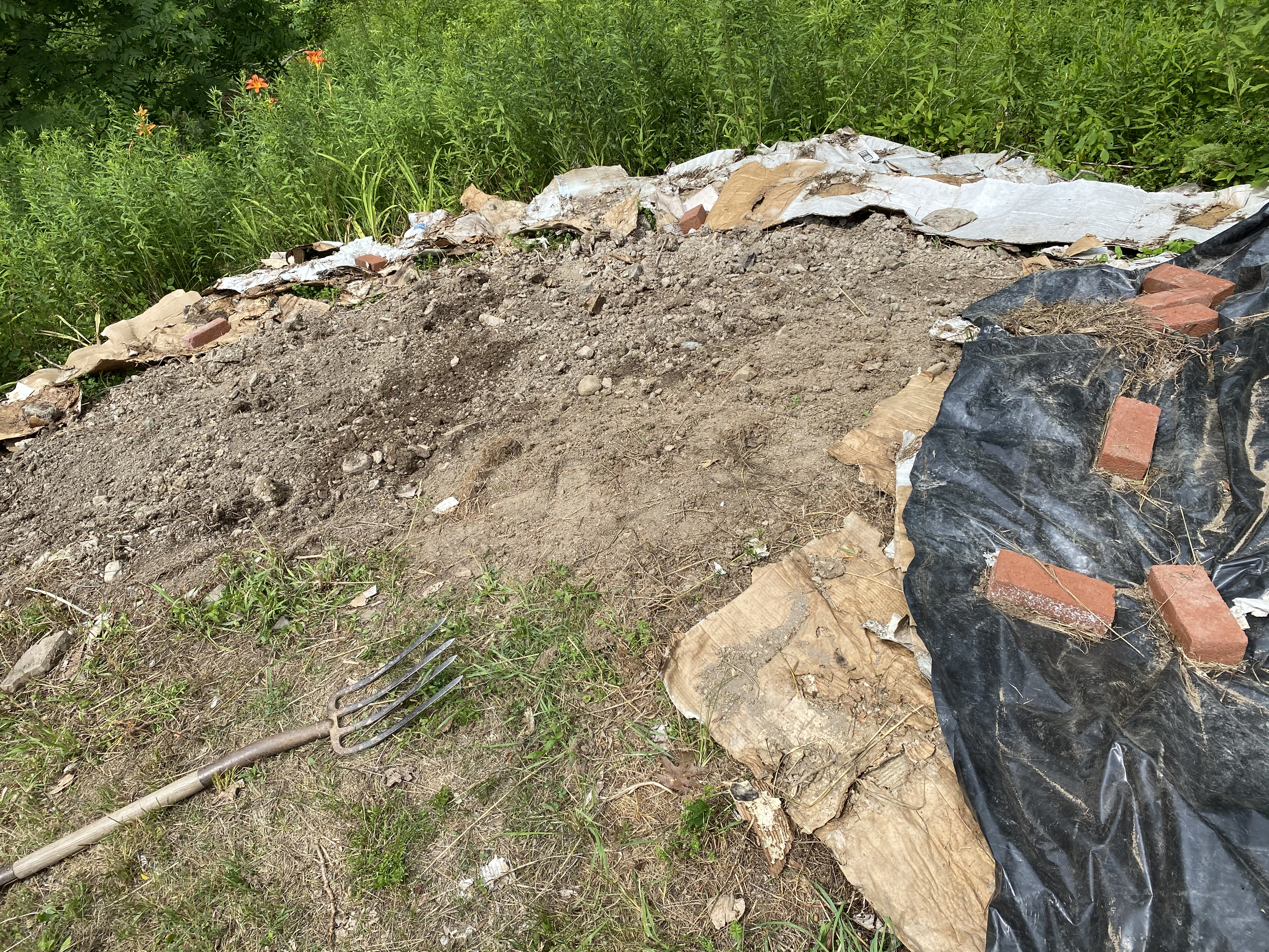 bare soil to be planted into, surrounded by covered soil for future plantings