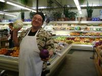 A smiling grocer showing off cabbages
