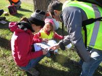 Participants in a winter ecology walk compare the winter buds on a plant specimen to those pictured in a guide.